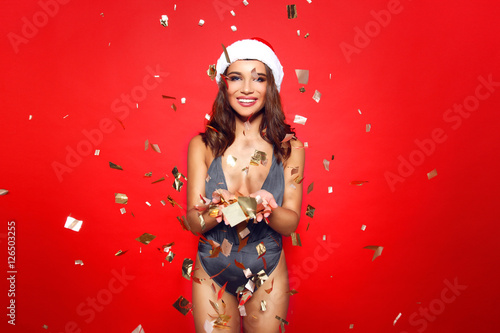 c3d91b80e2 beautiful young girl model stands on red background in sexy bathing suit  bikini and a Christmas Santa hat.on the background of flying golden ...