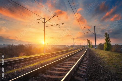 Keuken foto achterwand Spoorlijn Railway station against beautiful sky at sunset. Industrial landscape with railroad, colorful blue sky with red clouds, sun, trees and green grass. Railway junction. Heavy industry. Evening in autumn