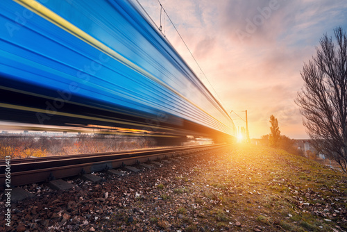 Montage in der Fensternische Eisenbahnschienen High speed blue passenger train on railroad track in motion at sunset. Blurred commuter train. Railway station. Railroad travel, railway tourism. Industrial landscape in the evening in autumn. Concept