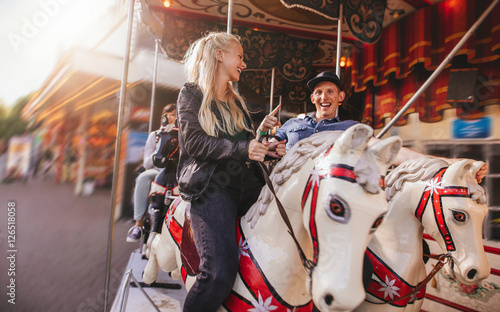 Foto Young couple on amusement park carousel