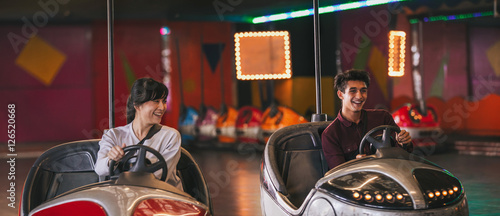 Poster Attraction parc Two young friends riding bumper cars at amusement park