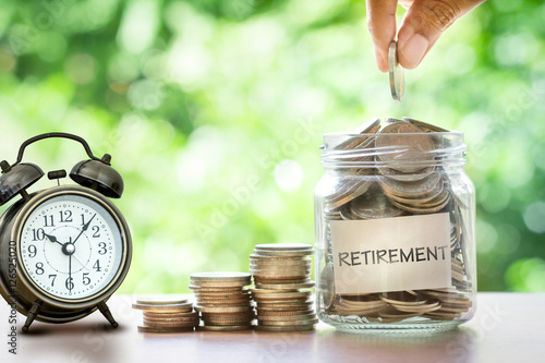 Fotografía  Hand putting Coins in glass jar with retro alarm clock , retirement