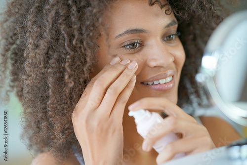 Fotografía  Portrait of beautiful mixed-race woman applying cosmetics on her face