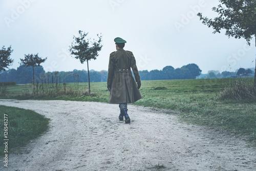 Fotografía  Rear view of vintage 1940s military officer walking on rural roa
