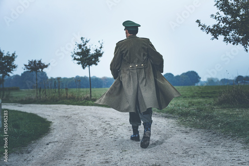 Fotografia  Rear view of vintage 1940s military officer walking on rural roa