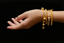 Woman's Hand With Many Different Golden Bracelets On Black Backg