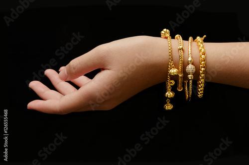 Tableau sur Toile woman's hand with many different golden bracelets on black backg