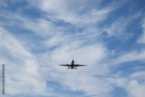 Photo Airplane with extended landing gear approaches airport