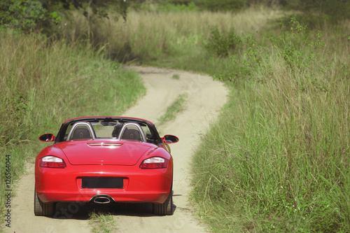 Red sports car on rural road Poster
