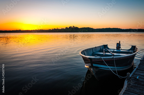 Canvas-taulu fishing boat on tranquil lake at sunset in Minnesota