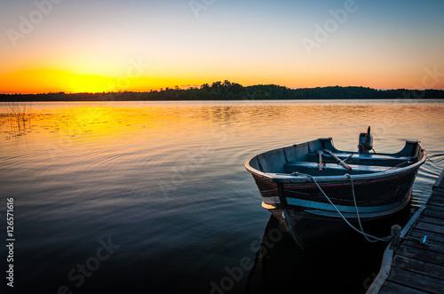 Obraz na plátne fishing boat on tranquil lake at sunset in Minnesota