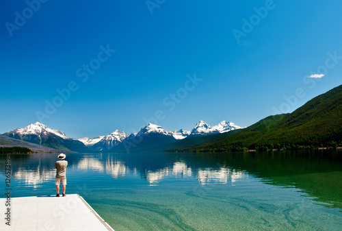 Fotografia, Obraz  Man looking at the majestic snow-capped mountains reflecting in the calm waters