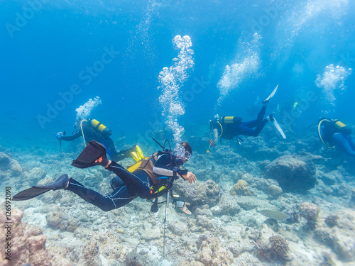 Staande foto Dolfijnen Group of underwater scuba divers with guide, Maldives