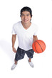A man holds a basketball and smiles at the camera