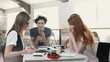 Multiethnic group of happy business people working together while sitting at table in office