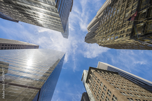Abstract city skyline view from below looking up to blue sky between an intersection of skyscrapers