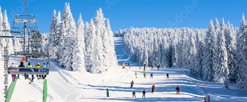 Panorama of ski resort, slope, people on the ski lift, skiers on the piste among white snow pine trees