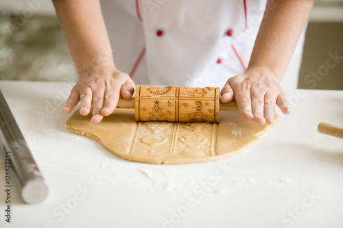 Close up of professional confectioner hands rolling thing