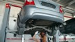 Tilt down of tired female technician fixing car bottom, finishing job and wiping forehead in the repair garage