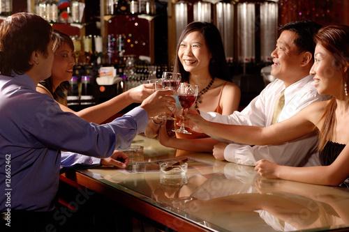 Fototapeta Men and women sitting around table toasting obraz na płótnie