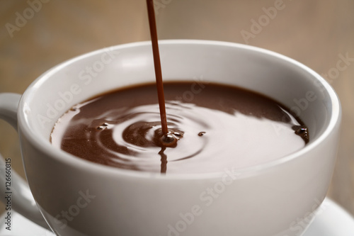 Foto op Canvas Chocolade hot chocolate pouring in cup