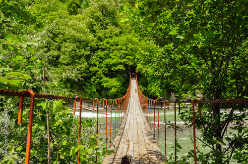 Spoed Fotobehang Begraafplaats Suspension bridge over the stormy mountain river