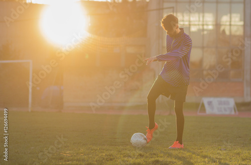 Juliste  young football player shooting soccer ball. grass field sun, sun