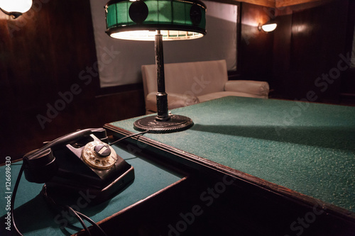 Photo  Vintage telephone and reading lamp on a table with green cloth