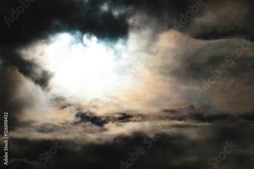 Fotografie, Obraz  Die Sonne scheint durch dunkle graue Gewitterwolken und erzeugt ein buntes Farbs