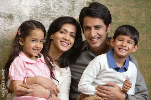 Photo  family of four smile at camera