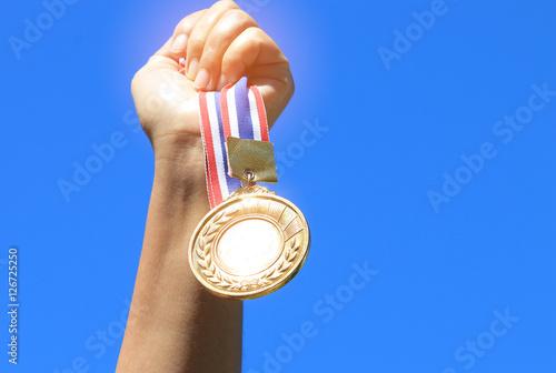 Fotografie, Obraz  hand raised and holding gold medal against blue sky. award conce
