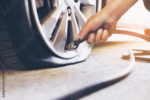 Obraz na plátně Technician is repairing car flat tire