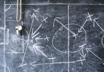 whistle of a soccer or football referee on black board with tactical diagram