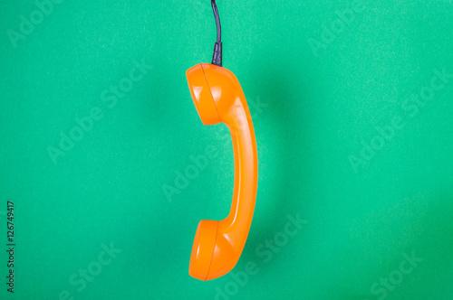Fototapeta Orange handset on a green background obraz na płótnie
