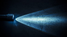 Flashlight And A Beam Of Light In Darkness. A Modern Led Light With Bright Projection On Dark Stone Surface. Surface With Copy Space.