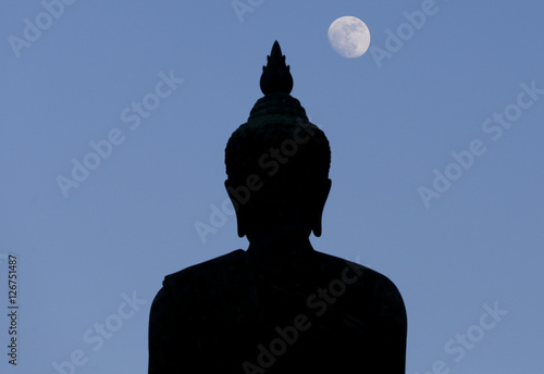 Fotografija  A moon shines in a sky over a large silhouetted Buddha statue in Bangkok, Thailand