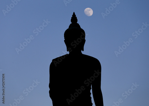 A moon shines in a sky over a large silhouetted Buddha statue in Bangkok, Thailand Poster