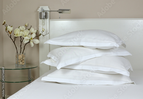 Fotografie, Obraz  Pile of comfortable pillows in white linen on a bedhead