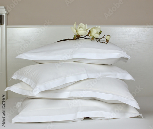 Fotografija Pile of comfortable pillows in white linen on a bedhead with artificial orchid d