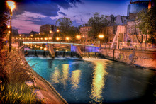 The Dambovita River In Bucharest, Romania. Photo Taken At Dusk With Turquoise Reflections In The Water. Also City Lights And A Luminated Bridge In The Middle.