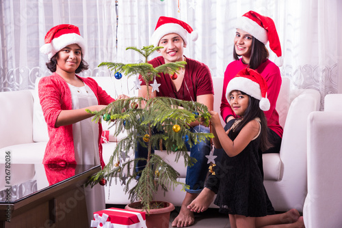 family christmas holidays and people concept happy indian kids decorating christmas tree