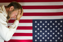Presidential Election Disbelief.  Man With Head In Hands In Front Of An Upside Down American Flag.  Protest Concept.