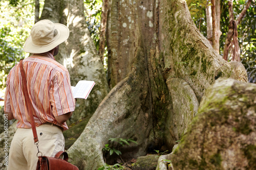 Photo  Rear view of Caucasian male biologist wearing hat and leather bag exploring jung