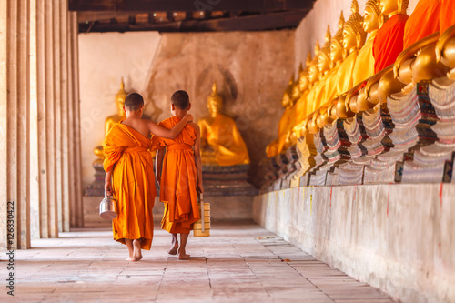 Fotografia  Two novices walking return and talking in old temple at sunset time, Ayutthaya P