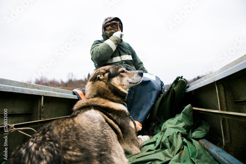 Fotobehang Jacht Male hunter swims on a boat with a hunting dog. Cold weather. A man dressed in a warm jacket and hat. Big gray dog Laika.