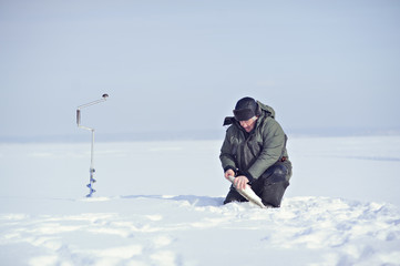 Fototapeta na wymiar Fisherman in winter on the ice caught fish.