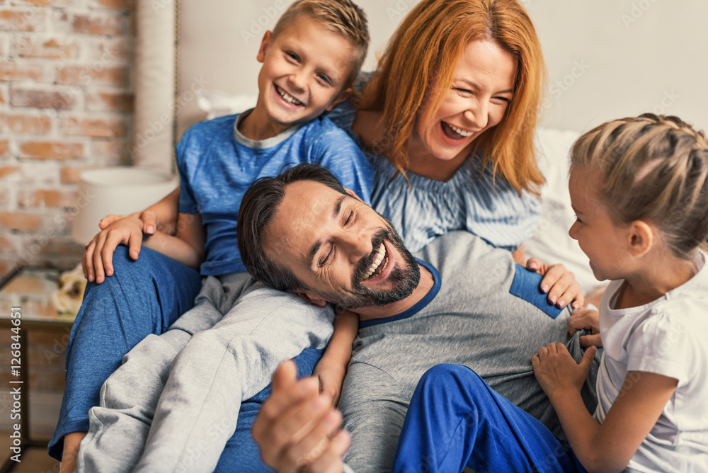 Fototapety, obrazy: Happy family lying down on bed at home