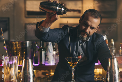 Barman is making cocktail at night club. Fototapeta