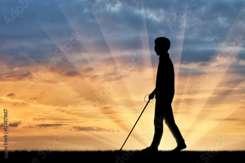 Disabled blind goes with cane on sunset Canvas Print