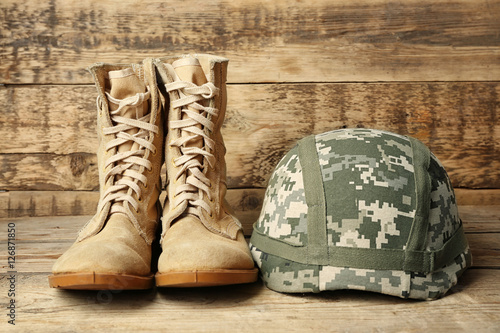 Fotografía  Pair of combat boots and military helmet on wooden background, close up